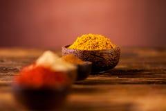Épices colorées dans des cuvettes en bois Photos stock