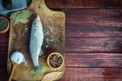 Épices d'éperlan de poisson frais pour faire cuire sur un panneau de cuisine Images stock