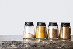 Épices de poudre dans des pots sur le bureau en bois et le fond clair photographie stock