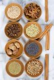 Épices et graines dans des cuvettes en bois Images stock