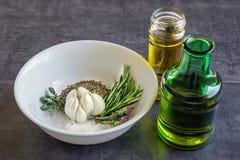 Épices et herbes dans une cuvette blanche, à côté des bouteilles d'huile d'olive Photos libres de droits