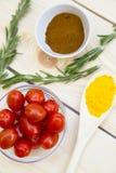 Épices et herbes sèches en pot en verre avec du liège, bol de tomates-cerises et poivrons de piment, fond blanc photographie stock