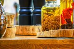 Épices et ingrédients d'herbes dans des bouteilles en verre décoratives, décoration de cuisine images stock