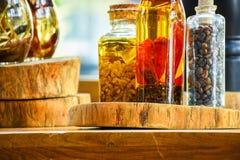Épices et ingrédients d'herbes dans des bouteilles en verre décoratives, décoration de cuisine image libre de droits