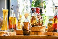 Épices et ingrédients d'herbes dans des bouteilles en verre décoratives, décoration de cuisine photo stock