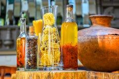 Épices et ingrédients d'herbes dans des bouteilles en verre décoratives, décoration de cuisine photos stock