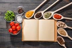 Épices et livre ouvert des recettes sur un fond en bois foncé, dessus Photographie stock