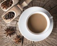 Épices pour les boissons chaudes sur le tronçon d'arbre de fente à côté d'une tasse de café chaud avec de la crème Images libres de droits