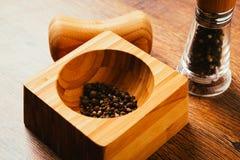 Épicez le mélange des poivrons en mortier sur un fond en bois Image libre de droits