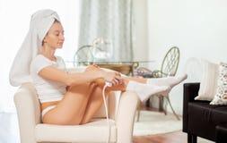 Épilation de laser epilation Femme enlevant des cheveux sur ses jambes à la maison images stock