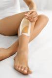 Épilation Longues jambes de femme avec la bande de cire dessus Dépilage Image stock