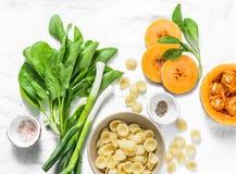 Épinards frais, potiron, pâte-ingrédients d'orekiette pour un déjeuner végétarien sur un fond clair, vue supérieure Sain, nourrit Photos stock