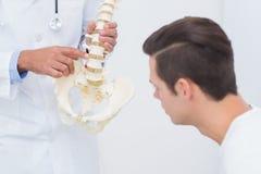 Épine anatomique de explication de docteur à son patient Image stock