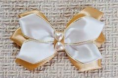 Épingle à cheveux pour un arc de blanc et de couleur d'or sur le fond du tissu brut, plan rapproché tiré photographie stock