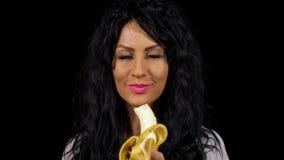 Épluchage de femme et banane de consommation banque de vidéos