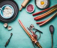 Épluchage de rhubarbe La rhubarbe rouge fraîche égrappe avec l'éplucheuse sur le fond de table de cuisine avec les outils à cuire images libres de droits