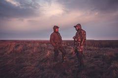 Época de caça dos caçadores no campo rural no nascer do sol imagens de stock royalty free