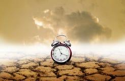 Época del concepto de la adversidad, despertador con la tierra seca fotografía de archivo