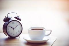Épocas del café con el despertador en la tabla foto de archivo