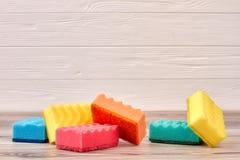 Éponges colorées de nettoyage sur le fond en bois Image stock