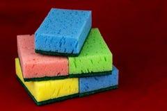 Éponges de nettoyage de ménage sur un tissu rouge Photo stock
