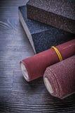 Éponges de ponçage roulées de papier d'émeris sur des abras de panneau en bois de vintage Photo libre de droits