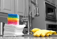 Éponges et gants colorés dans la cuisine Photographie stock