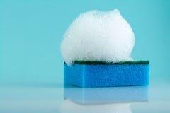 Éponges, mousse, bulles, fond bleu-clair Photos stock