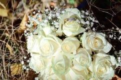 Épousant l'or les anneaux se trouvent sur le bouquet de la jeune mariée photos libres de droits