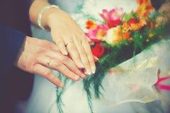 Épousant, la main de jeunes mariés dans des bagues de fiançailles Image stock