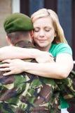 Épouse étreignant la maison de mari d'armée sur le congé Photographie stock libre de droits