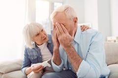 Épouse affectueuse consolant son mari sanglotant photographie stock