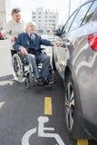 Épouse aidant le mari handicapé obtenant dans la voiture Photo libre de droits