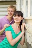 Épouse d'étreinte de mari près de maison en bois de village Photographie stock
