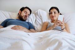 Épouse de fraude à l'aide du téléphone portable se trouvant dans le lit à côté de son sleepi Photos libres de droits