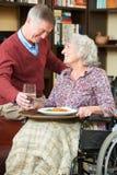 Épouse de portion d'homme supérieur dans le fauteuil roulant avec le repas Photographie stock
