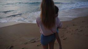 Épouse de tir de père de mouvement lent et petite fille au bord de la mer banque de vidéos