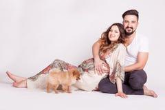 Épouse enceinte à côté de mari et de leur petit chien Image stock