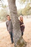 Épouse enceinte avec le mari à côté de l'arbre Photos stock