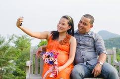 Épouse enceinte et mari prenant la photo de téléphone portable Image libre de droits