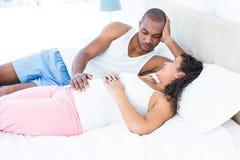 Épouse enceinte heureuse détendant avec le mari sur le lit photographie stock libre de droits