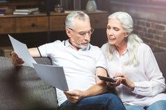 Épouse et mari comptant leurs factures images stock