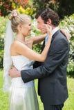 Épouse heureuse touchant sa nouvelle joue de maris Photographie stock