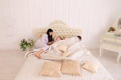 Épouse hurlant à la fille, mari dormant sur le lit blanc dans la chambre photographie stock
