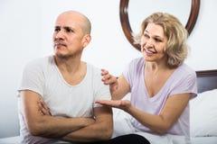 Épouse soulageant chaudement le mari bouleversé dans la chambre à coucher Image libre de droits