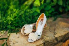 Épouser des chaussures à une frontière en pierre sur un fond des feuilles vertes Photo libre de droits