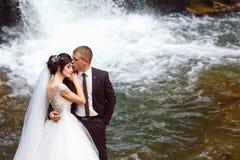 Épouser des couples embrassant et étreignant sur des roches près de la belle cascade grande en montagne photographie stock libre de droits