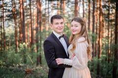Épouser des couples se tient entre les arbres de haute montagne Photographie stock