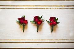 Épouser l'ensemble de trois boutonnieres des roses rouges sur la table Photographie stock libre de droits