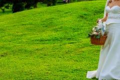 Épouser la fille tient un panier des pétales photographie stock